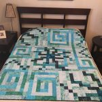 teal universe quilt on a bed